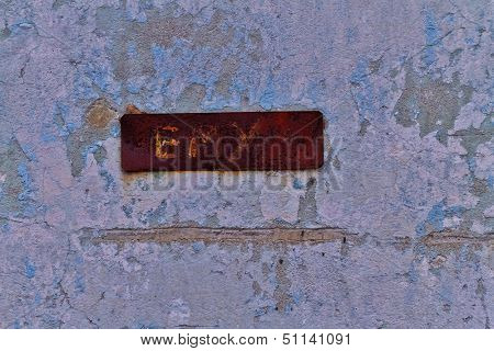 Rusty plate on wall shriveled
