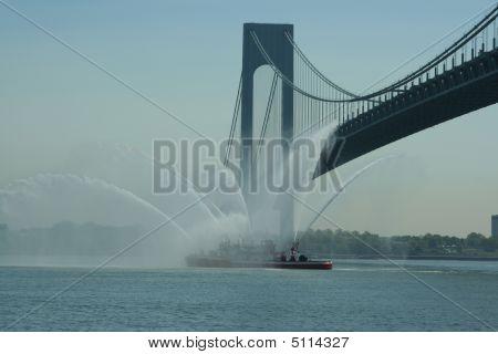 Fire Boat Under Bridge Spraying Water.