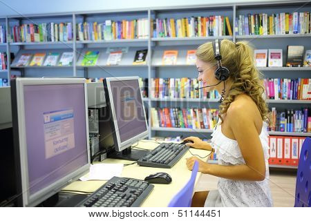 A happy beautiful woman wearing headphones looking at a computer in the library