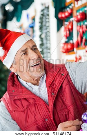 Senior male owner in Santa hat working at Christmas store