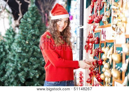 Portrait of beautiful woman in Santa hat buying Christmas ornaments at store
