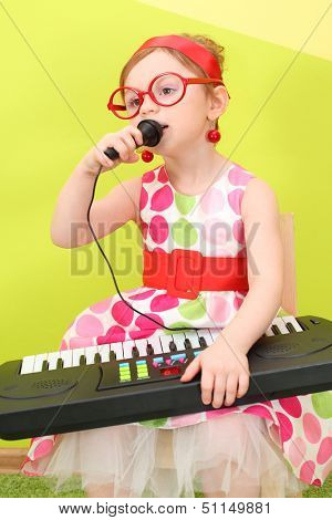 Mod girl in a bright dress and big round glasses singing into a microphone on her lap toy piano