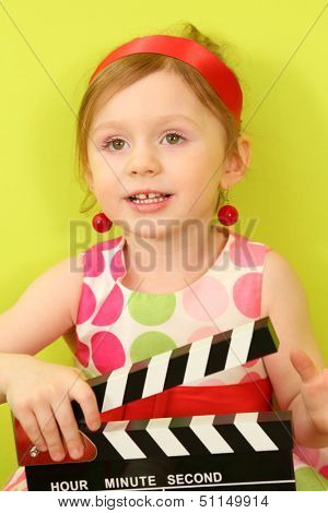 A little girl in a red headband and a large earrings with clapboard