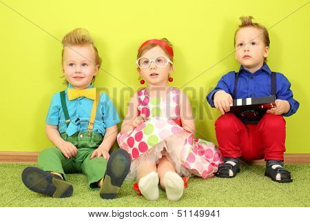 Three mods children in bright clothes sitting at the bright green wall