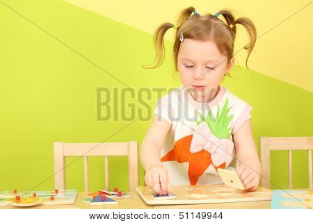 Little girl with pigtails sitting at the table and do wooden puzzle