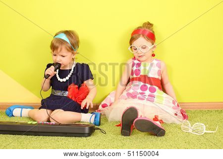 Mods two girls sitting at the bright green wall in front of toy piano