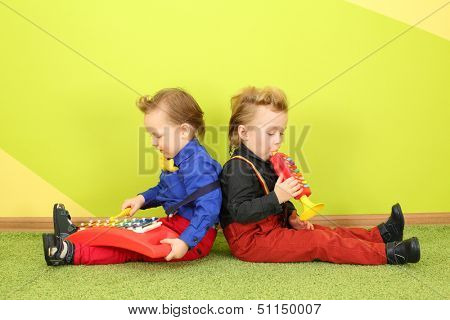 Two boys are sitting back to back and playing on a childrens trumpet and metallophone