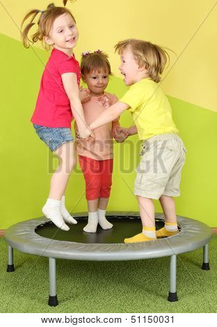 Three smiling children jumping on a trampoline holding hands