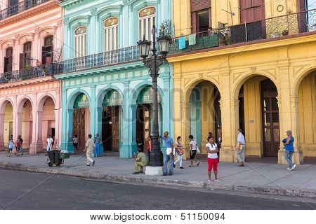 HAVANA-SEPTEMBER 10:Cubans in a street sidelined by colorful buildings September 10,2013 in Havana.With over 2 million inhabitants,Havana is the capital of Cuba and the largest city of the Caribbean