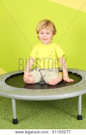 A smiling little boy sitting on a trampoline in a bright room