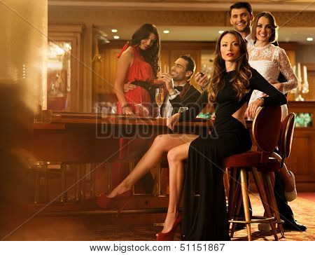 Group of young people behind table in a luxury interior