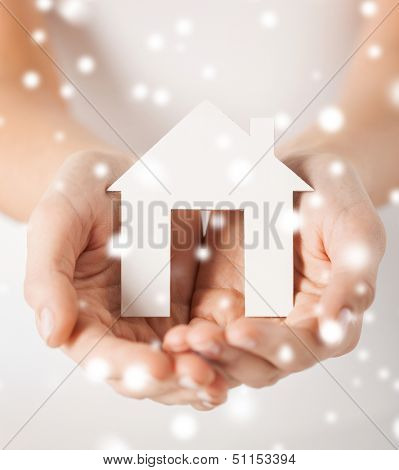 closeup pi??ture of woman hands holding paper house