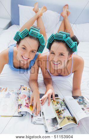 Happy friends in hair rollers lying in bed looking and smiling at camera at sleepover