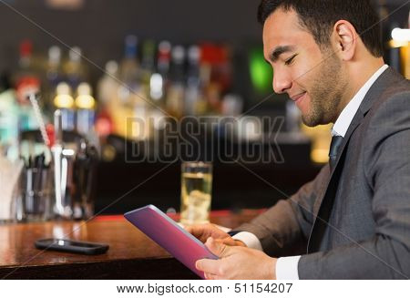 Close up of businessman sitting at bar and reading drinks menu