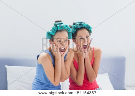 Friends with hair rollers on sitting in bed and screaming at sleepover