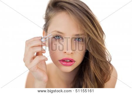 Concentrated brunette model plucking her eyebrows on white background