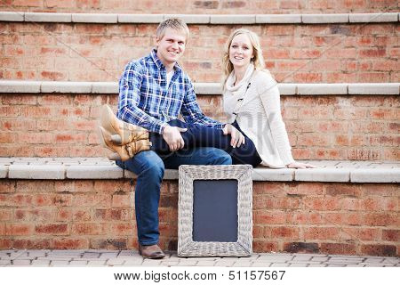Attractive Caucasian Couple Sitting Next To Blackboard