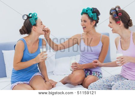 Laughing friends sitting in bed having milk and cookies at sleepover