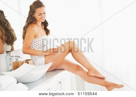 Happy Young Woman Sitting In Bathroom And Examining Leg