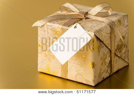 Christmas present with ribbon and blank tag on gold background copyspace