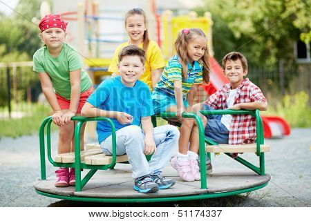 Image of cute friends having fun on carousel outdoors