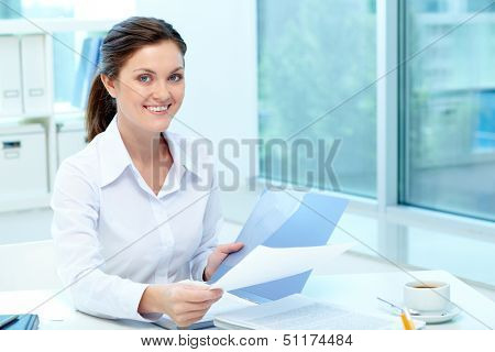 Portrait of happy employer holding test results and looking at camera