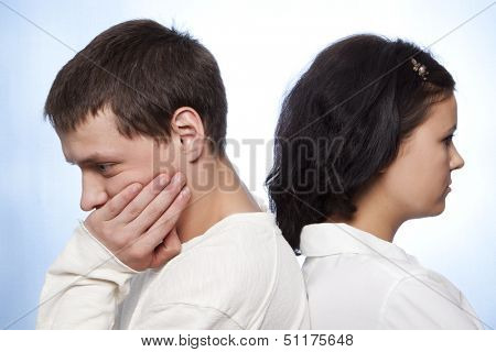 Young couple quarreling against a blue background