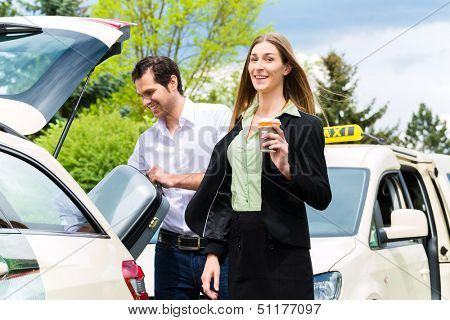 Young woman standing in front of taxi, she has reached her destination, the taxi driver will help with the luggage