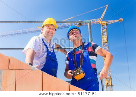 Two proud construction site workers or bricklayers standing on house project directing the crane with a remote control