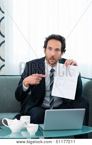Businessman working in the hotel, on a contract or document and is confused about it