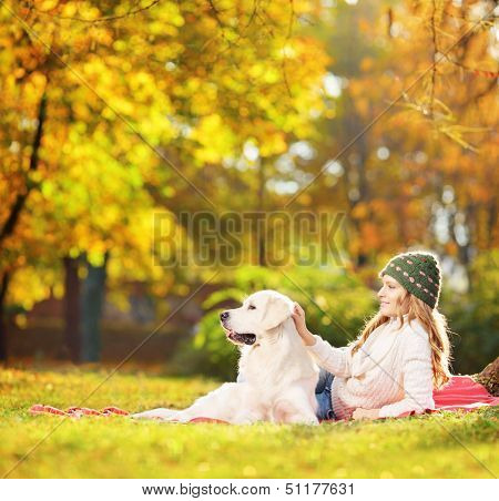 Female lying on a green grass with her labrador retriever dog in a park, shot with a tilt and shift lens
