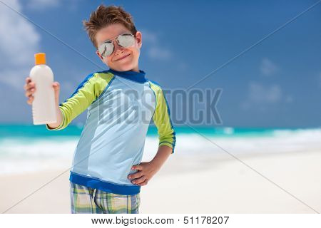 Cute little boy at tropical beach holding a bottle of sunblock