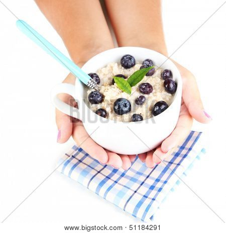 Oatmeal in cup with berries in hands isolated on white