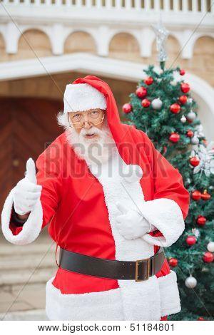 Portrait of confident Santa Claus gesturing thumbsup against Christmas tree