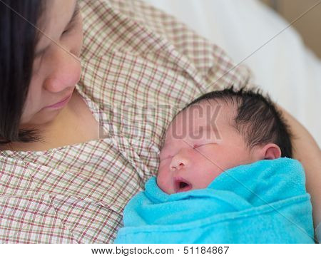 Newborn Asian baby girl sleeping in mother's arms, inside hospital room