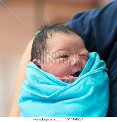 Newborn Asian baby girl smiling in father's arms, inside hospital room
