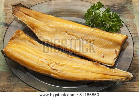 smoked trout fillet on a glass plate with parsley leaf