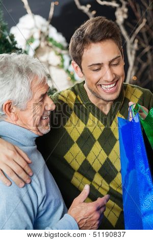Happy father and son with shopping bags in Christmas store