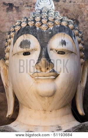 Head detail of old Buddha statue in the Wat Si Chum temple in Sukhothai historic park, Thailand