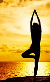 stock photo of natarajasana  - Woman doing yoga during sunset - JPG