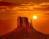 image of arid  - Monument Valley West Mitten at sunrise sun orange sky Utah photo mount - JPG