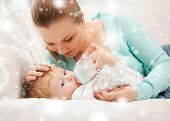 family, children, christmas, x-mas, love concept - happy mother and adorable baby with feeding-bottl