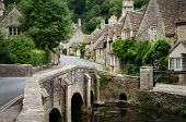 stock photo of quaint  - The quaint fairy tale village of Castle Combe at the border between the Cotswolds and Wiltshire with its characteristic bridge - JPG