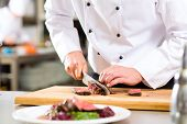 stock photo of plating  - Chef in hotel or restaurant kitchen cooking - JPG