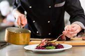 foto of adults only  - Chef in hotel or restaurant kitchen cooking - JPG