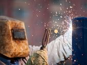 picture of protective eyewear  - Heavy industry welder worker in protective mask hand holding arc welding torch working on metal construction - JPG