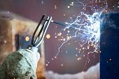 foto of welding  - Heavy industry welder worker in protective mask hand holding arc welding torch working on metal construction - JPG