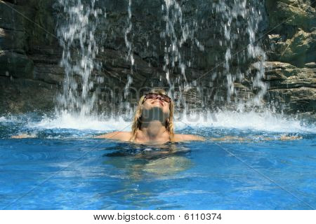 Woman under waterfall