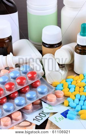Prescription drugs on money background representing rising health care costs. On wooden background