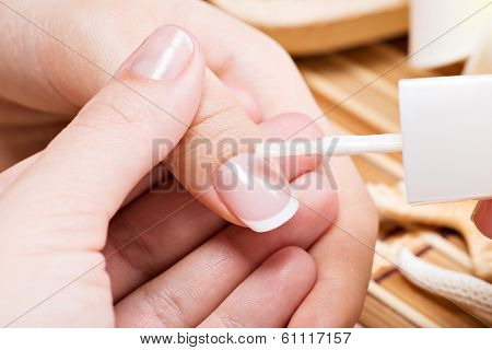 Beautician Applying Nail Varnish On A Thumbnail.